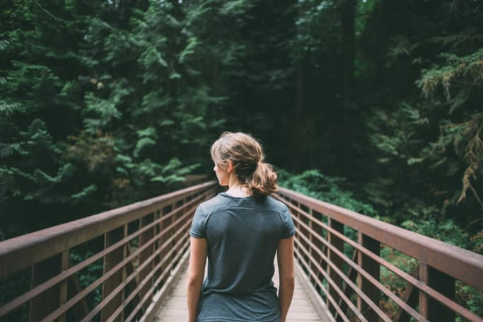 selective focus photography of woman in black t-shirt standing on bridge